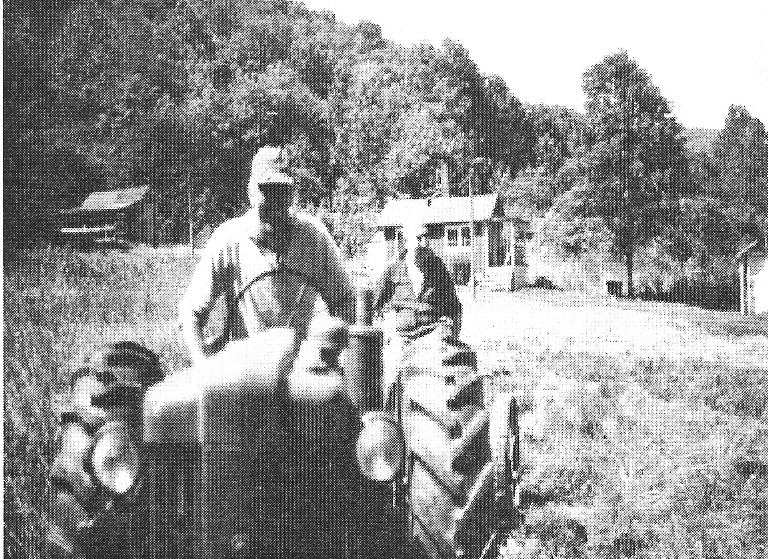 Mahlon Korns' house in the background, Bobby Shroyer on tractor