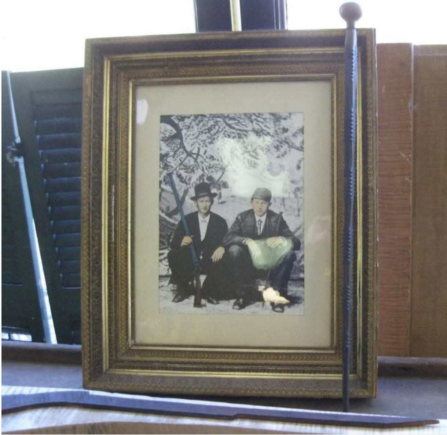 This photo shows a framed picture of David and Milton Defibaugh in their youth, with one holding a full stock long arm and the other holding a small pistol.